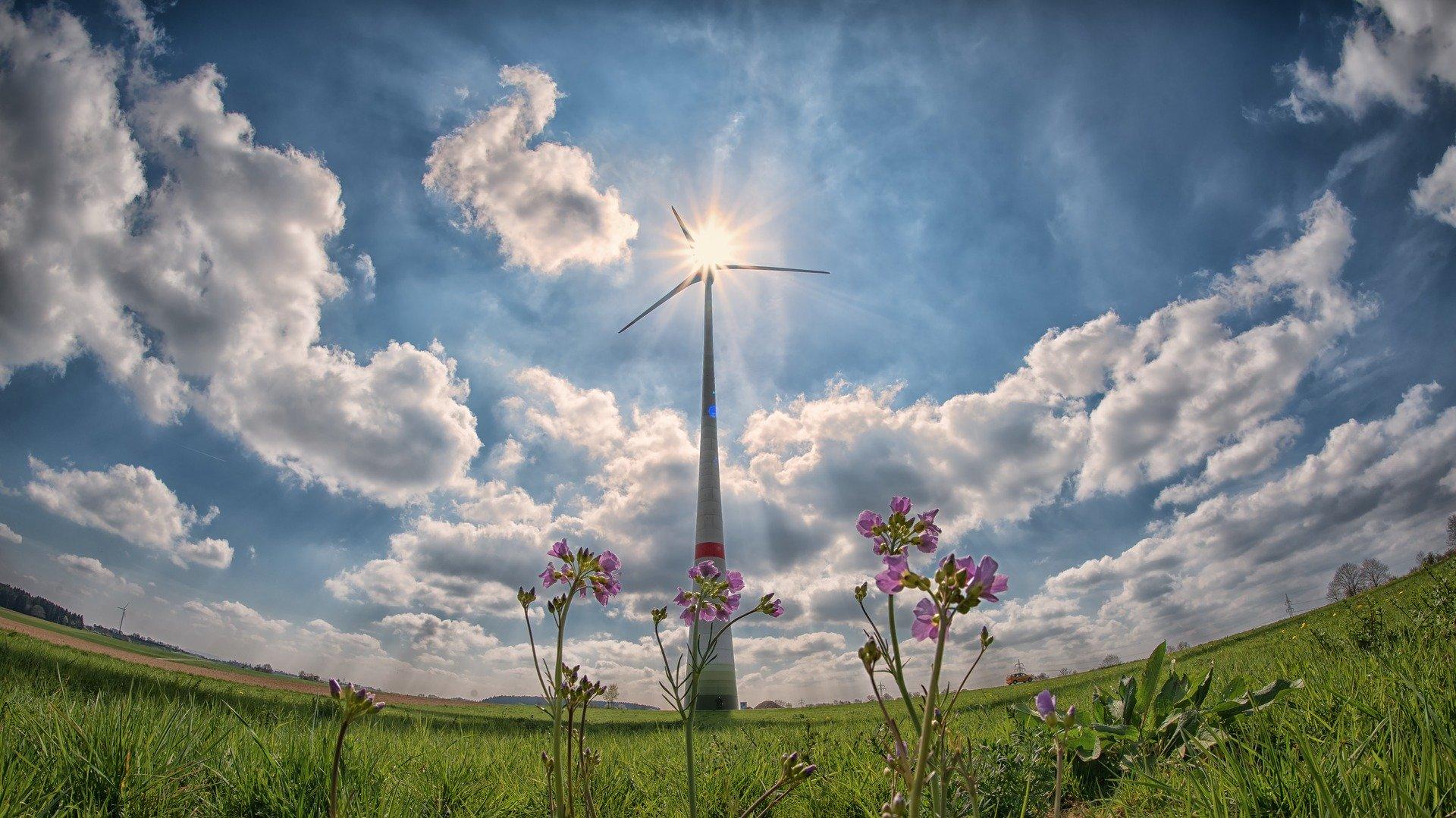 Ein Windrad mit Wolken und Wiese